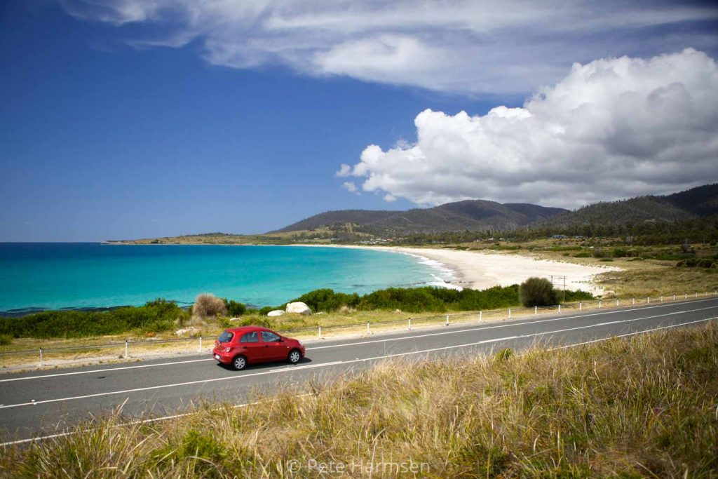 Red car driving the East Coast on their Lap of Tasmania